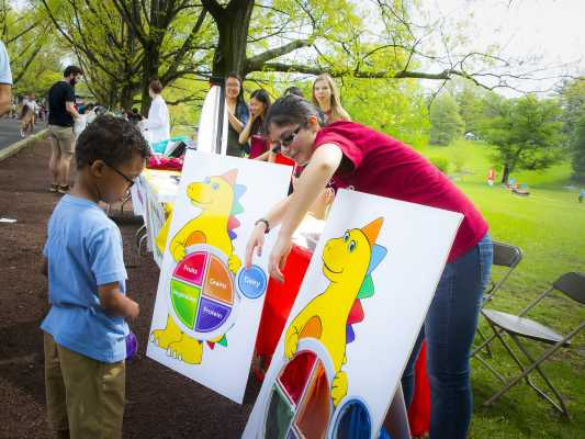 A visiting child takes a try at nutrition game wheel on the Cook campus during Rutgers Day